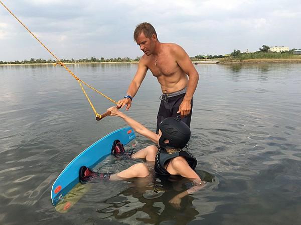 Инструктор А. Якушев обучает новичка скольжению на доске.